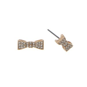 "Dainty gold tone stud earrings featuring a bow accented with clear rhinestones. Approximately 1/2"" wide."