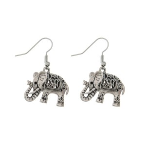 "Silver tone fishhook earrings featuring an elephant. Approximately 1"" in length."