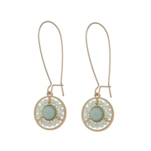 "Gold tone hook earrings featuring a mint green beaded circle pendant. Approximately 3"" in length."