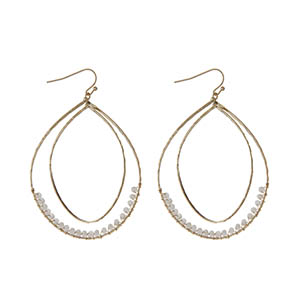 """Gold tone fishhook earrings featuring a hammered curved teardrop with ivory wire wrapped beads. Approximately 3"""" in length."""