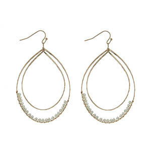 """Gold tone fishhook earrings featuring a hammered curved teardrop with mint green wire wrapped beads. Approximately 3"""" in length."""