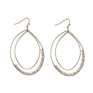 """Gold tone fishhook earrings with a hammered curved teardrop with champagne wire wrapped beads. Approximately 3"""" in length."""