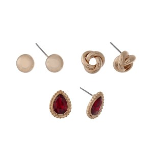 Gold tone three pair earring set with polished circle studs, knot studs, and red teardrop studs.