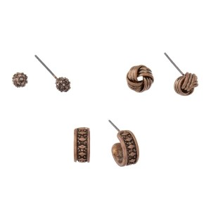 Burnished gold tone three pair earring set with pave circle studs, knot studs, and hoops.