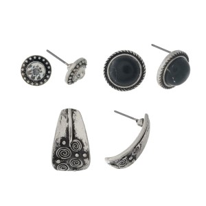 Burnished silver tone three pair earrings with clear rhinestones, black circles, and textured studs.