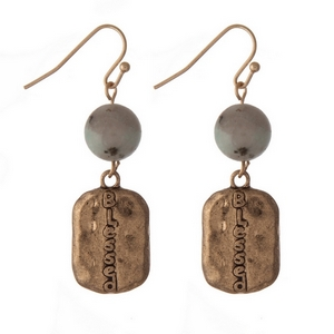 "Gold tone fishhook earrings stamped with ""Blessed"" and accented with a kiwi natural stone bead. Approximately 1.25"" in length."