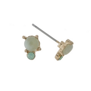 "Dainty gold tone stud earrings with a green stone accented by an opal rhinestone. Approximately 1/4"" in length."