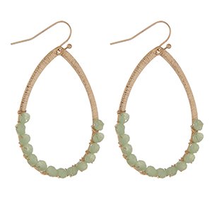 """Gold tone teardrop earrings with light green faceted beads. Approximately 1.25"""" in length."""