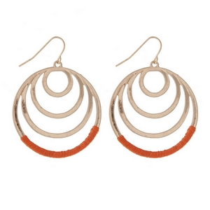 """Gold tone fishhook earrings with cascading circles and orange thread. Approximately 1.25"""" in length."""