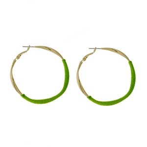 """Gold tone twisted hoop earrings with lime green thread accents. Approximately 2"""" in diameter."""