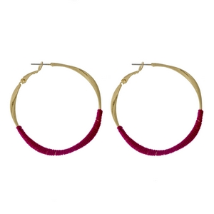 """Gold tone twisted hoop earrings with magenta thread accents. Approximately 2"""" in diameter."""