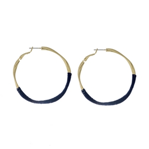 """Gold tone twisted hoop earrings with navy blue thread accents. Approximately 2"""" in diameter."""