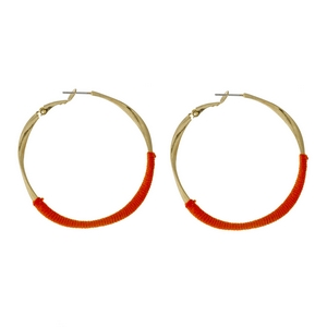"""Gold tone twisted hoop earrings with orange thread accents. Approximately 2"""" in diameter."""