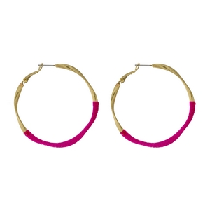 """Gold tone twisted hoop earrings with pink thread accents. Approximately 2"""" in diameter."""