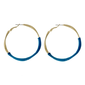 """Gold tone twisted hoop earrings with teal thread accents. Approximately 2"""" in diameter."""