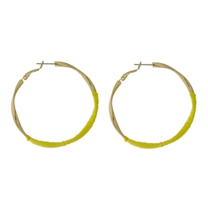 """Gold tone twisted hoop earrings with yellow thread accents. Approximately 2"""" in diameter."""