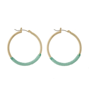 "Gold tone hoop earrings with mint green thread accents. Approximately 1.5"" in diameter."