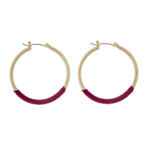 "Gold tone hoop earrings with magenta thread accents. Approximately 1.5"" in diameter."