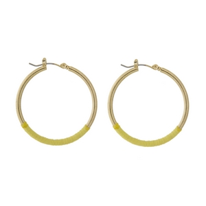 "Gold tone hoop earrings with yellow thread accents. Approximately 1.5"" in diameter."
