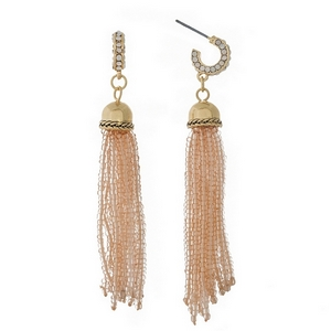 "Gold tone earrings featuring a peach beaded tassel. Approximately 3"" in length."