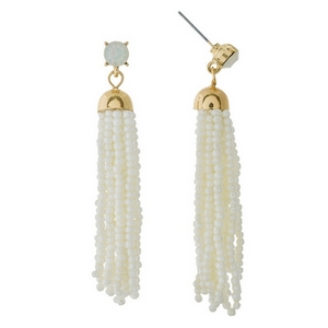 "Gold tone post style earrings featuring a white beaded tassel and rhinestone accent. Approximately 2.5"" in length."