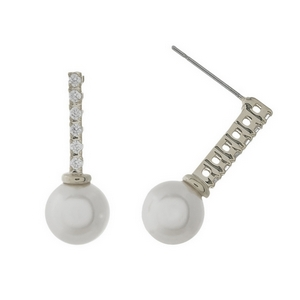 "Silver tone stud earrings featuring a clear rhinestone bar and a pearl bead. Approximately 1"" in length."