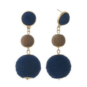 "Gold tone post style earrings with two navy blue thread wrapped beads and a wooden bead. Approximately 2.75"" in length."
