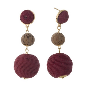 "Gold tone post style earrings with two burgundy thread wrapped beads and a wooden bead. Approximately 2.75"" in length."