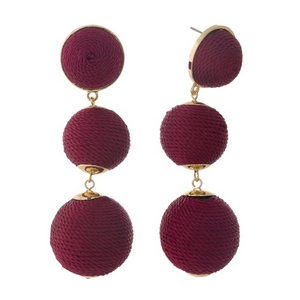 "Gold tone post style earrings with burgundy thread wrapped beads. Approximately 3"" in length."