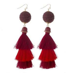 "Gold tone fishhook earrings with a two tone, red, tapered tassel. Approximately 4.25"" in length."