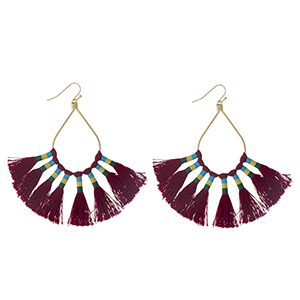 "Gold tone fishhook earrings with an open oval shape and eight burgundy thread tassels. Approximately 3.25"" in length."