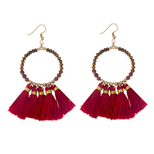 "Gold tone fishhook earrings with a natural stone beaded circle, accented with red thread tassels. Approximately 3"" in length."