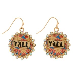 "Burnished fishhook earrings with a circle shape, patterned background stamped with ""Y'all"" and iridescent rhinestones. Approximately 3/4"" in diameter."