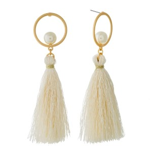"Gold tone circle stud earrings with a pearl bead accent and thread tassel. Approximately 3.5"" in length."