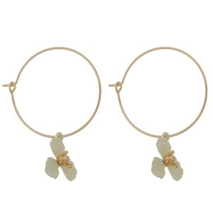 "Dainty gold tone hoop earrings with a flower charm. Approximately 1.25"" in length."