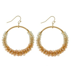 "Gold tone post earrings with an open circle shape and wire-wrapped, two tone beading. Approximately 2.5"" in length."