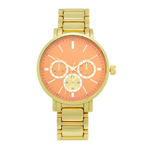 "Gold tone metal band watch featuring a 1 1/2"" orange plated watch face."
