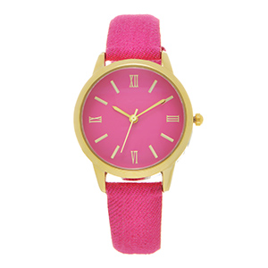 "Hot pink denim fabric watch band featuring a gold tone 1 1/8"" watch face."