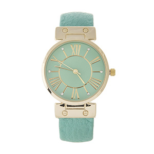 Mint green cuff watch with gold tone accents.