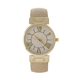 Tan cuff watch with gold tone accents.