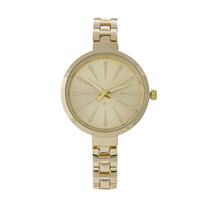 Gold tone watch with a clear rhinestone.
