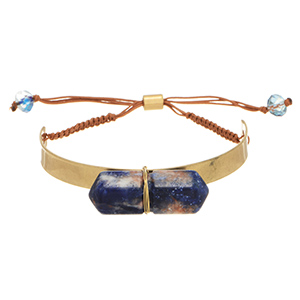 Worn Gold tone metal focal accenting a marbleized blue tone quartz with a brown tone pull tie adjustable back.