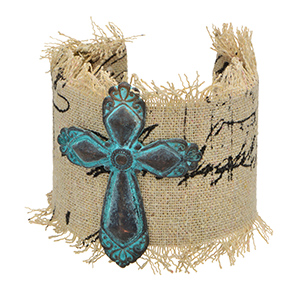 Gold tone cuff bracelet wrapped in fabric featuring a patina cross focal.
