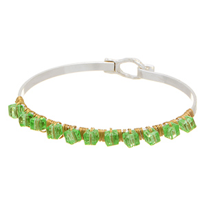 Worn silver tone latch bracelet with green cubes wrapped with gold tone wire.