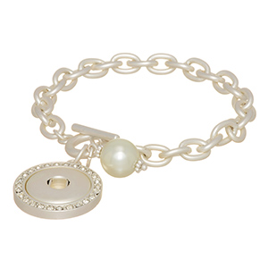"Matte silver tone toggle bracelet featuring a faux ivory pearl and a rhinestone disk with a snap for snap-on charms. Snap jewelry collection. Approximately 7"" in length."