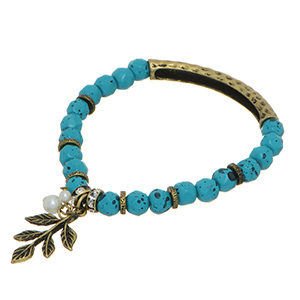 Stretch bracelet featuring turquoise beads with burnished gold tone leaf charm and faux pearls.