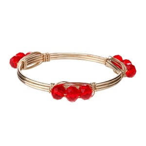 Wire wrapped bangle bracelet with red acrylic beads. Made of zinc alloy. Nickel and lead free. One size fits most.