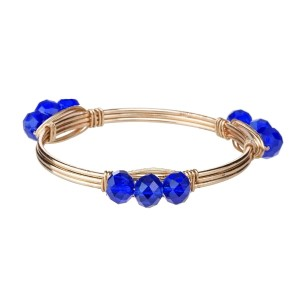 Wire wrapped bangle bracelet with royal blue acrylic beads. Made of zinc alloy. Nickel and lead free. One size fits most.