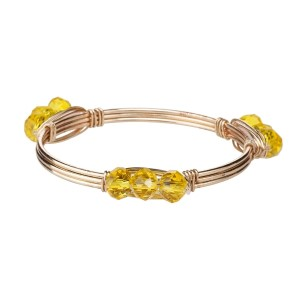 Wire wrapped bangle bracelet with yellow acrylic beads. Made of zinc alloy. Nickel and lead free. One size fits most.