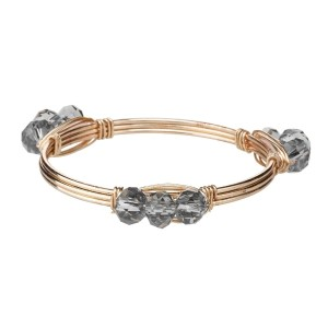 Wire wrapped bangle bracelet with gray acrylic beads. Made of zinc alloy. Nickel and lead free. One size fits most.